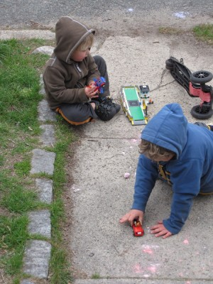 Harvey and Zion playing with legos on the front walk