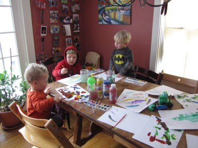 the boys painting at the kitchen table; lots of papers covered already
