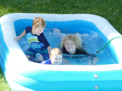 the boys splashing in an inflatable pool