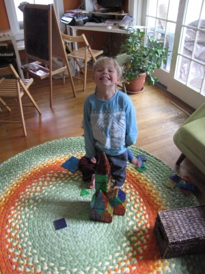 Zion smiling (sort of) with his magnatiles construction on the new rug