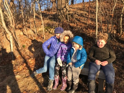 Harvey and Zion sitting on a bench with Nisia and Grandma