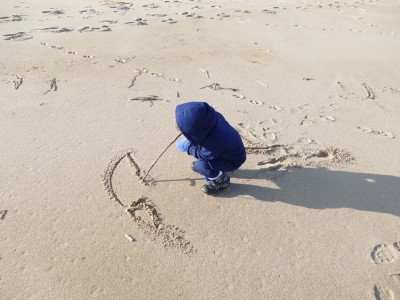 Lijah drawing in the sand with a stick