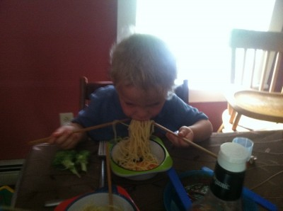 Zion eating spaghetti with chopsticks--one in each hand