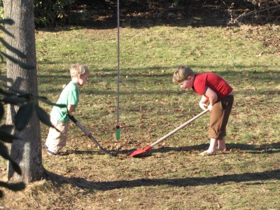 Harvey and Zion, barefoot and short-sleeved, digging in the lawn