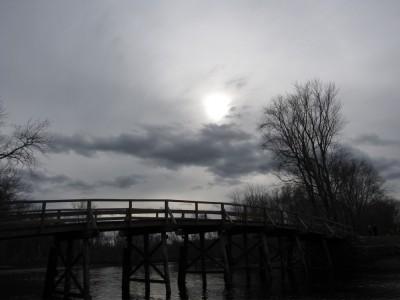 bare trees and gray sky behind the Old North Bridge
