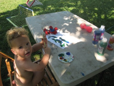 naked Lijah woeking on painting on a table outside