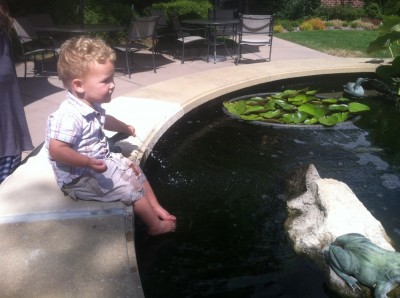 Lijah sitting on the side of the koi pool at the nursing home