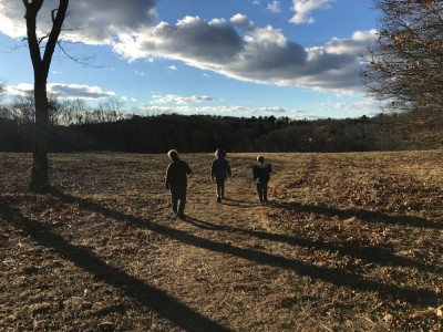 Harvey, Zion, and Nisia walking in a field