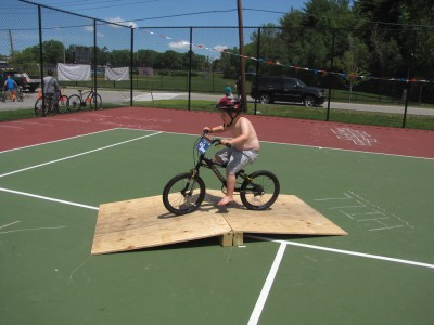Harvey riding over a wooden ramp on the tennis court