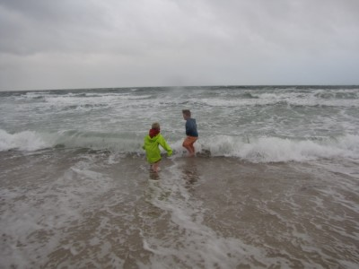 Harvey and Zion wading in the stormy ocean