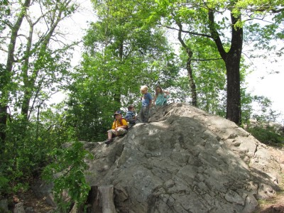 the kids atop a mountainous boulder