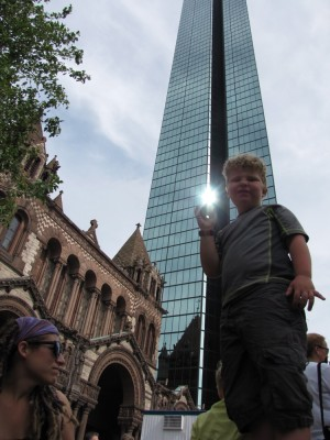 Harvey standing on a pedestal, with Trinity Church and the Prudential Tower behind him