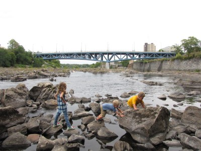 Harvey, Zion, and Havana clambering on rocks on the edge of the Merrimack River in Lowell