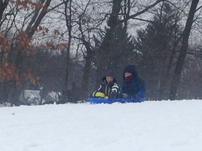 Harvey and Zion sledding in the snow