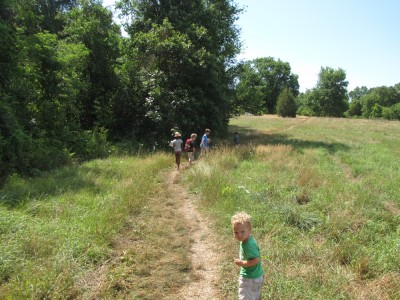 Lijah following behind the other kids on a meadowy hike
