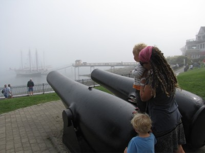 Zion, Mama, and Lijah looking down the cannons at the fog-bound ships