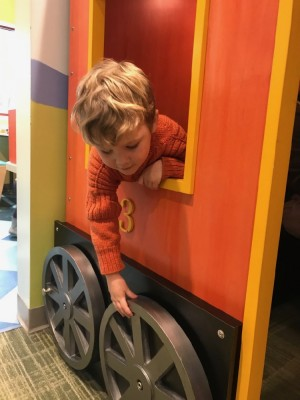 Lijah, in his orange sweater, leaning out the window of the orange play train at the museum