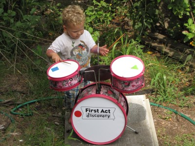 Lijah playing the drum kit outside