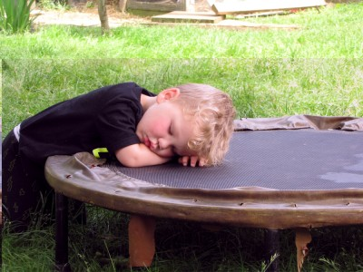 Lijah napping leaning on the trampoline outside