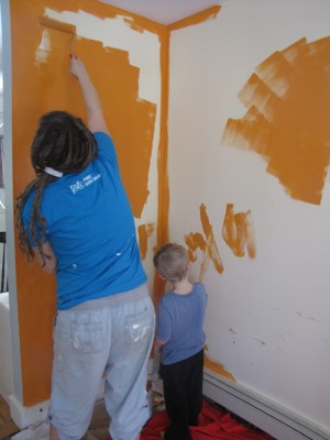 Leah and Zion painting the playroom walls orange