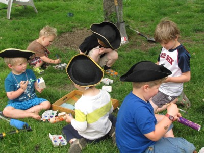 the kids, many in pirate hats, sitting on the grass painting