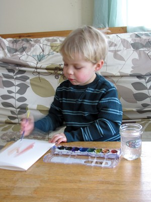Zion carefully painting in the playroom