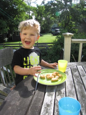 Lijah smiling at his seat at the back porch breakfast table
