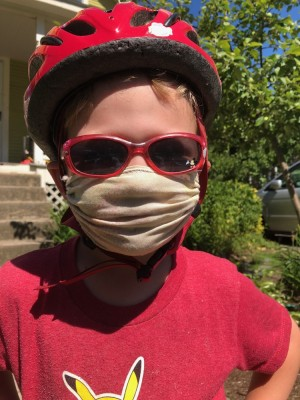 Lijah in his mask and red shirt, bike helmet, and sunglasses