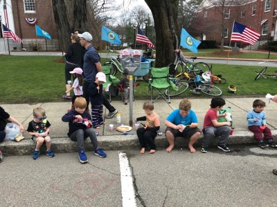 the kids sitting on the curb eating treats waiting for the parade