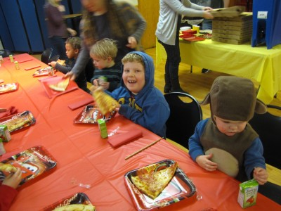 the three boys sitting at the birthday table, with pizza