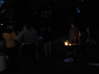 in the dark, guests gather around the fire in the kettle grill