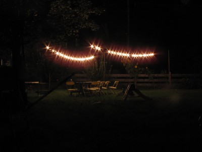 the globe lights hanging over the empty picnic table