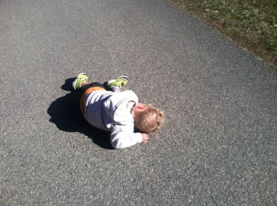 Lijah lying down on the paved path at Drumlin Farm