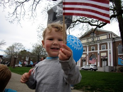 Lijah waving a flag along the parade route