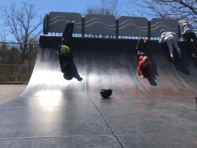 Zion and Elijah sliding head-first down a halfpipe
