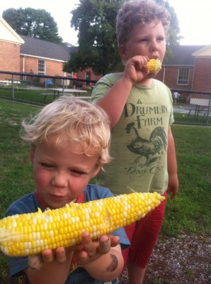 Zion and Harvey eating corn on the cob by the playground