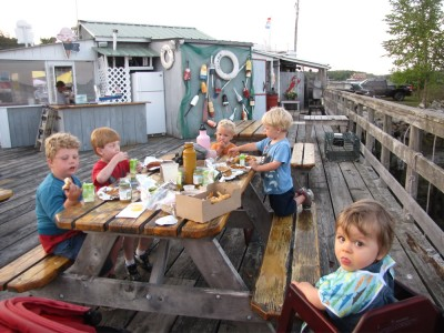five boys eating supper on the pier