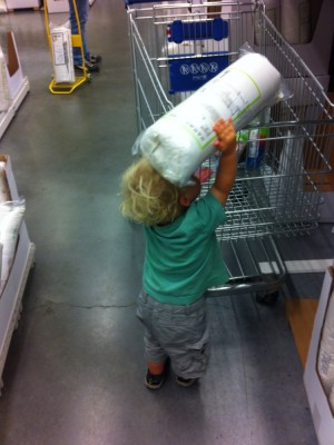 Zion putting his new pillow into the shopping cart