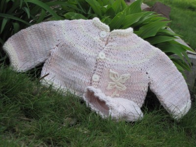 pink cotton baby sweater in garden
