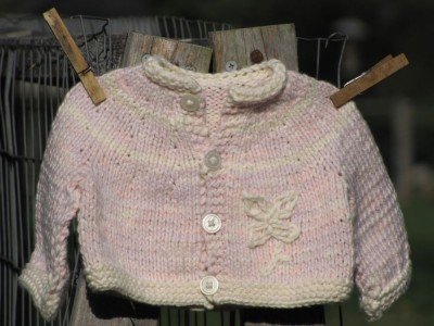 pink cotton sweater on clothes pins