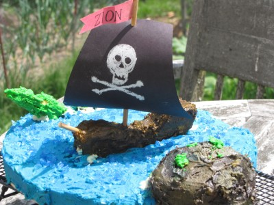 a cake: blue sea with island, sea monster, and pirate ship