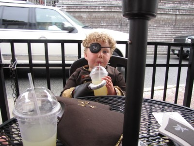 pirate Harvey sitting at an outdoor restaurant table, with a cup of lemonade clutched in his hook