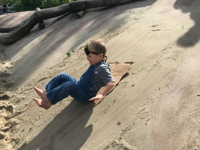 Lijah sliding down the sandy concrete slope at the Kemp Playground, wearing and eye patch
