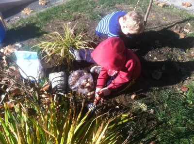 Zion and Lijah planting bulbs in the front yard