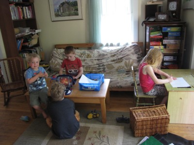 a relaxed group of kids playing board games and drawing in our playroom