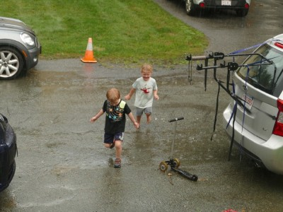 Lijah and Henry running on the street in the steady rain