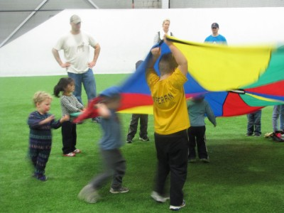 the boys playing with a parachute with some other kids