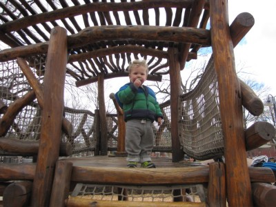 Lijah up on a boat playstructure made of logs