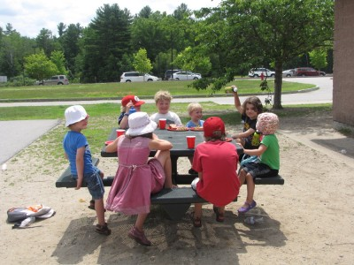 some of the kids sitting around a table on the playground