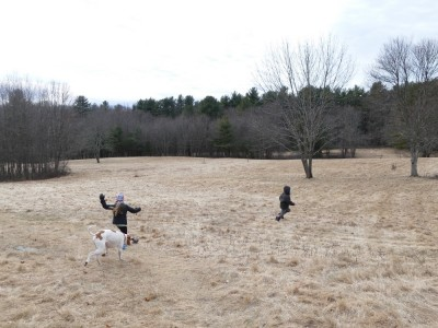 Lijah running in a field with a friends and her dog